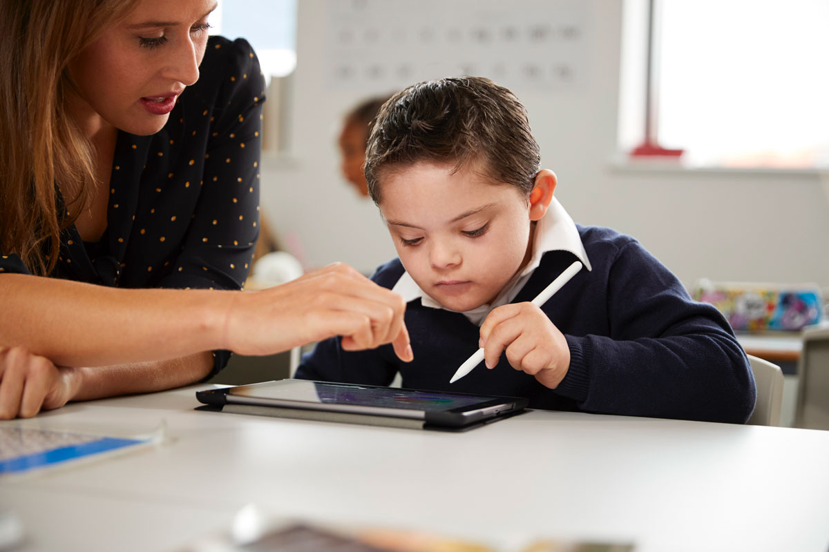 elementary school special needs student using tablet device with teacher
