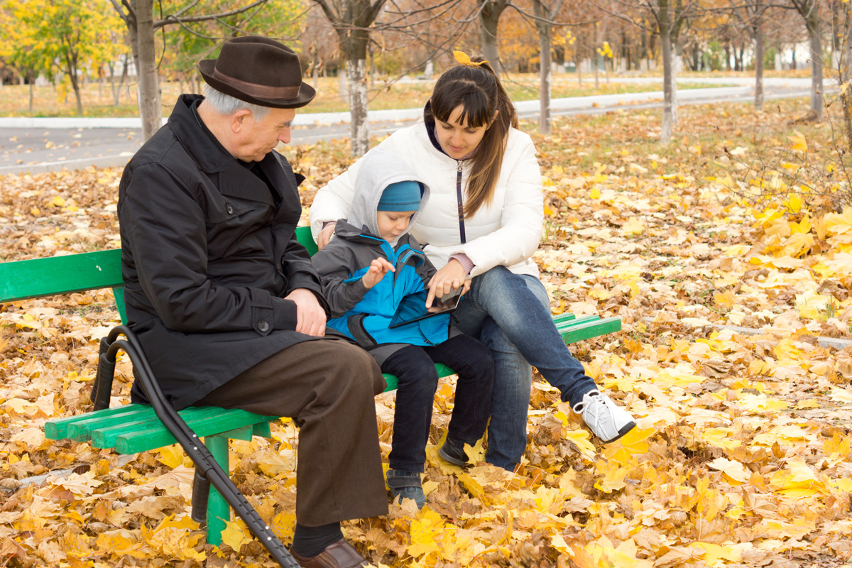grandparent and parent with child in park, reading tablet device